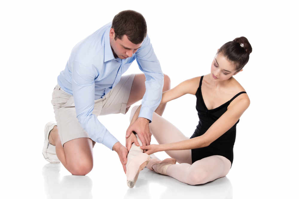 Beautiful female ballet dancer and physiotherapist isolated on a white background. Ballerina is wearing a black leotard, pointe shoes and pink stockings. Therapist is wearing a blue shirt and beige shorts.