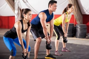 Three people working out with keetlebells in a crossfit gym
