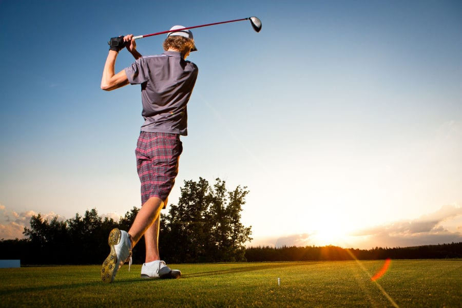 Male golf player teeing off golf ball from tee box to beautiful